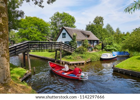 The picturesque village of 'Giethoorn' in the province of 'Overijssel', also called 'Venice of the North' because of the many water canals where tourists do their sightseeing from a boat #1142297666