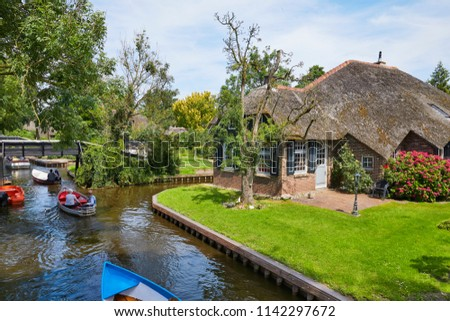 The picturesque village of 'Giethoorn' in the province of 'Overijssel', also called 'Venice of the North' because of the many water canals where tourists do their sightseeing from a boat #1142297672