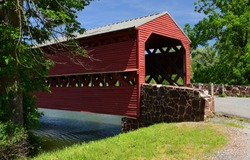 the picturesque, woodem, red  sachs covered bridge over marsh creek on a sunny summer day, near gettysburg, pennsylvania