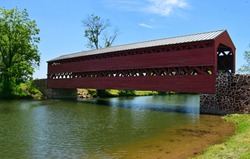 the picturesque, wooden, red  sachs covered bridge over marsh creek on a sunny summer day, near gettysburg, pennsylvania