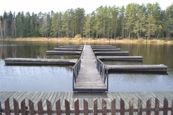 The pier and marina on pontoons reflecting in the water, with a walkway between the handrails against the backdrop of a pine forest.