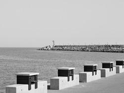 The pier of Pesaro harbor with a lighthouse, tetrapods and a series of wooden tables with stone benches placed on the edge (Pesaro, Italy, Europe)