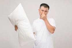 The pillow smells bad. Portrait Asian man holding white pillow and getting bad smell. Studio shot on grey background