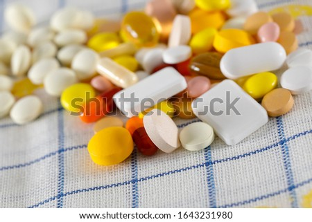 The pills are on the napkin. These varied tablets have various shapes and various colors.