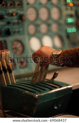 The pilot moves handle of throttle in the airliner
