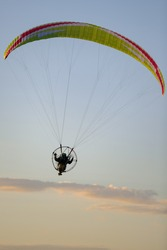 The pilot took off into the sky on an individual backpack parajet with a gasoline engine. Flying with a motorized wing. Extreme sports. Paralet and small aircraft.