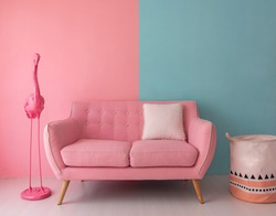 The pink sofa which has a white pillow is set in living room which has blue and pink wall.