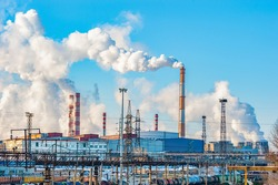 The pipes of the metallurgical plant, from which dirty smoke rises into the clear sky. Air pollution! Exhaust gases, depletion of the ozone layer,the greenhouse effect. An environmental disaster.