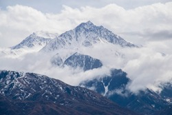 The piramidal mountain with rocks and ice in Tian Shan mountains in Central Asia near Almaty covered by clouds. Best place for active life, hiking and trekking in Kazakhstan. Best view from the window