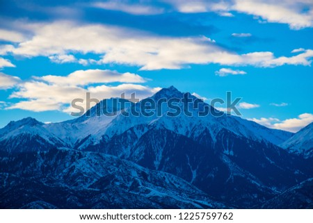 The piramidal mountain with rocks and ice in Tian Shan mountains near Almaty covered by clouds on dramatic dark sunrise sky. Best place for active life, hiking and trekking. Best view from the window.