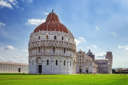 The Pisa Baptistery with the Cathedral and Leaning Tower of Pisa. Italy, June 2017. Famous Italian architecture.
