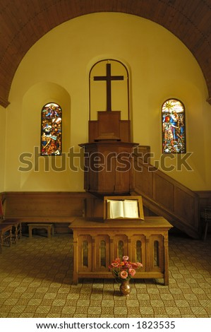 The plain pulpit in a small protestant church. In front of it stands a small wooden altar on which an open bible rests. Lit by the warm glow of a late afternoon sun coming in through the side windows.