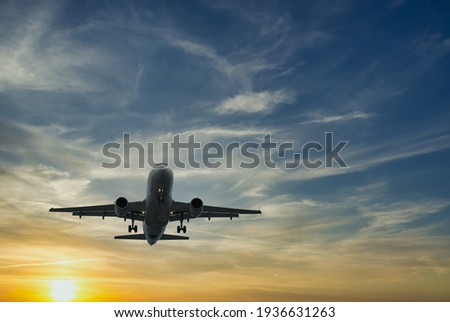 The plane against the blue sunset sky. The setting sun. Sunset.