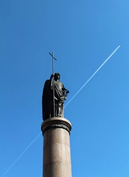 The plane flies against the background of the monument to the saint, Belarus