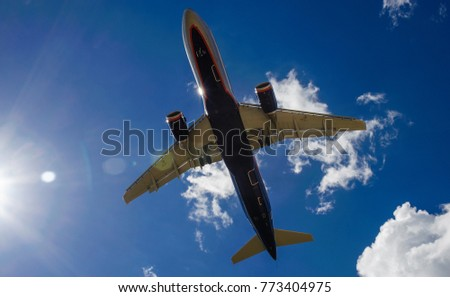 The plane on a background of blue sky and white clouds. #773404975