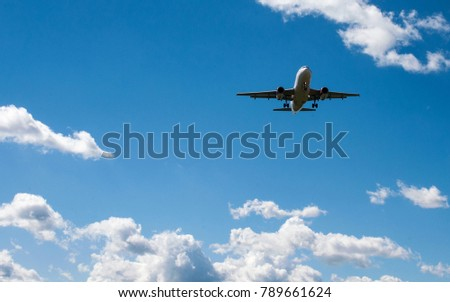 The plane on a background of blue sky and white clouds. #789661624