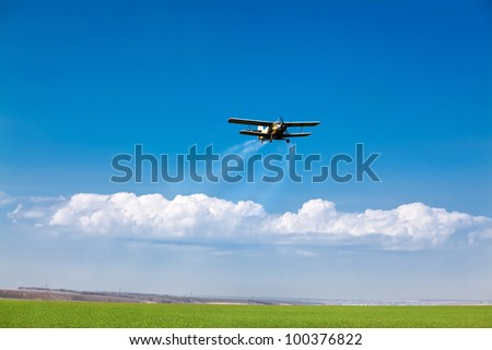 The plane over a field. Sprays fertilizers for a grass