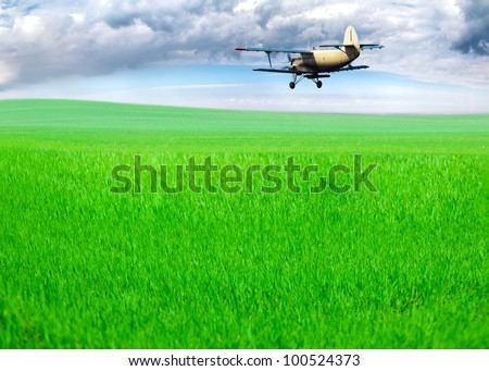 The plane over a field. Sprays fertilizers for a grass - stock photo