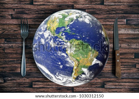 Photo of  The planet Earth plate with a fork and knife on a wooden background. World hunger concept. Feed the world.
