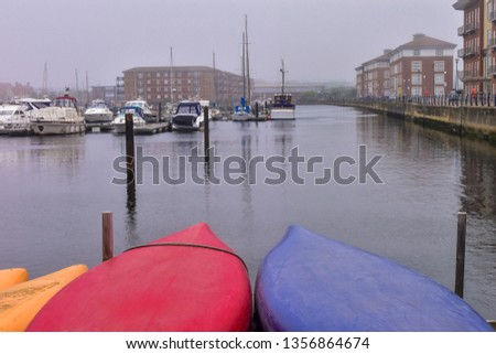 The plastic colorful red - blur canoes parking in the marina background yachts, buildings with reflections and cloudy sky in misty day. Concept Canoe.
