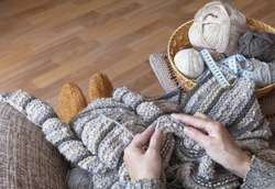 The pleasure of handicraft work. Woman knits a warm striped wool sweater on knitting needles. Nearby accessories for hand knit in wicker basket. Focus on knitted fabric, hands out of focus. Top view