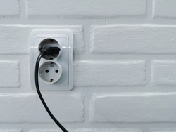 The plug is plugged into a euro socket. Black wire on a white wall. Electrical appliance plugged in