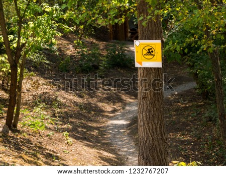 The pointer is attached to a tree trunk near a reservoir in the forest on the trail, swimming is prohibited. Symbol, sign, icon. #1232767207