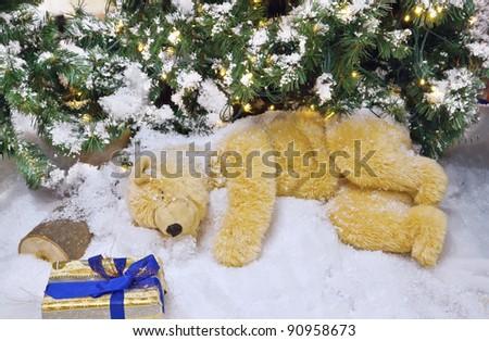 The polar bear is sleeping under the Christmas tree.