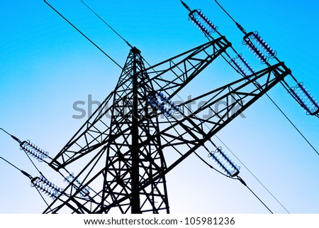 the poles of a power line against a blue sky. high voltage power line