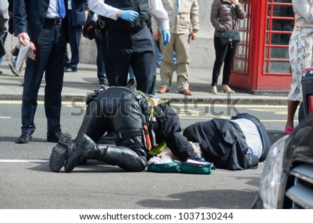 The policeman of London renders first aid to the pedestrian who suffered in the accident. #1037130244