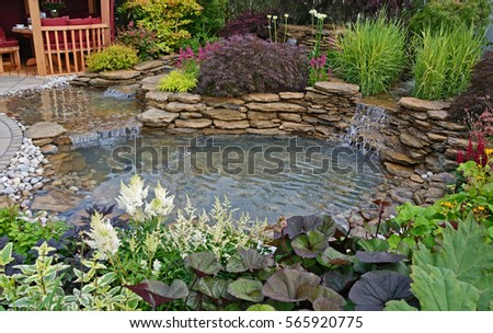 The pond area in an aquatic garden with planted rockery and waterfalls creating a water feature