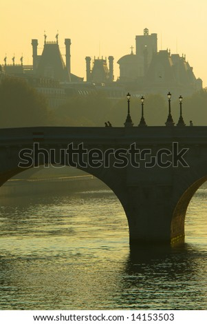 The Pont Neuf spans the Seine. The sun rises over the Town hall fine-cut roof, in the background. - stock photo