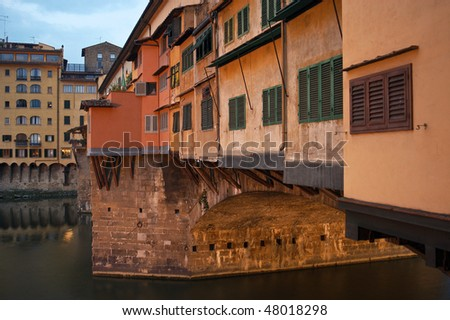 The Ponte Vecchio, famous old bridge in Florence, Italy, across the Arno River. The glow of sunrise is striking the bridge.