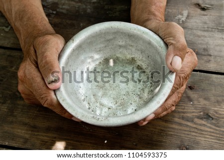 The poor old man's hands hold an empty bowl of beg you for help. The concept of hunger or poverty. Selective focus. Poverty in retirement. Alms Stock photo ©