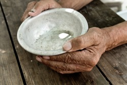 The poor old man's hands hold an empty bowl. The concept of hunger or poverty. Selective focus. Poverty in retirement. Alms