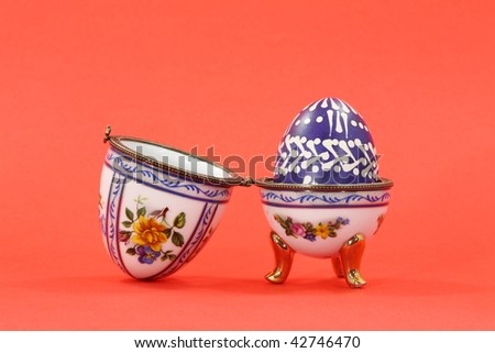 The porcelain- egg with Easter egg inside. On red separated.
