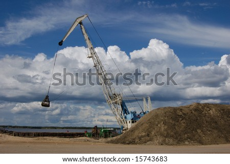 The port dredge unloads sand from the barge - stock photo
