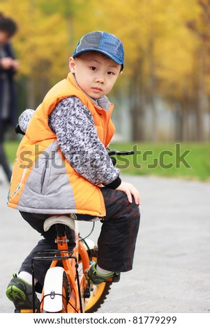 the portrait of an Asian boy ridding bicycle
