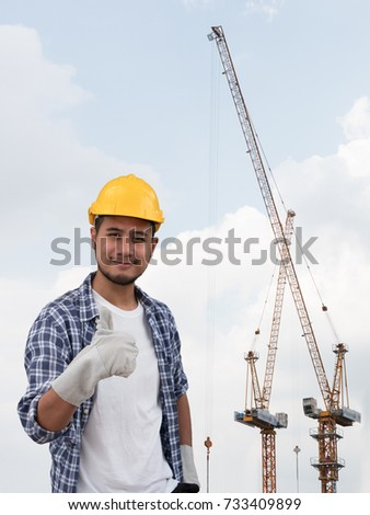 The portrait of Asian male engineer. The construction project engineer is observing tower crane operation at construction site. The isolated image of engineer with clipping path. Double exposure image