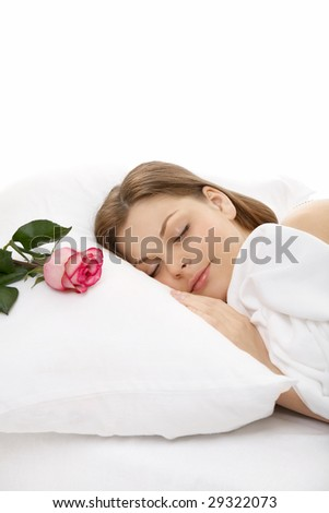 The portrait of the girl sleeping in bed, on a pillow lies a rose