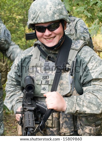 The portrait of the smiling US Army soldier with machine gun