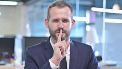 The Portrait of Young Businessman putting Finger on Lips