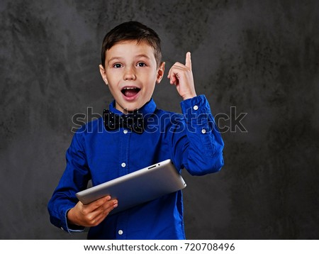 The positive teenager boy holds tablet PC over grey background. #720708496