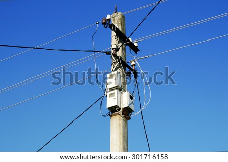 The post power lines with power line cables and electricity meters against the blue sky