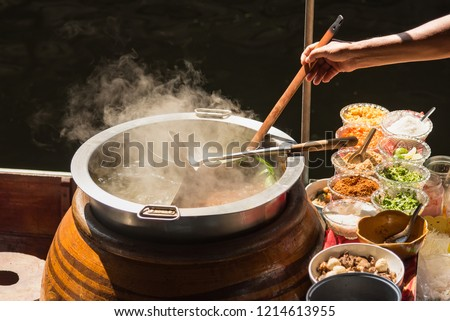 The pot is prepared for cooking. The noodles are in low-light, boiling water with white smoke and steam on black background