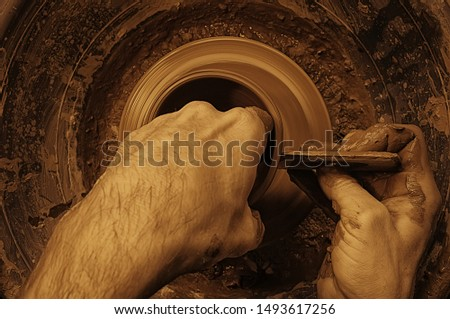 The potter creates a vase on a potter's wheel. In the master's hands the special potter's tool. Top view, pottery by the potter's eyes. The handicraftsman working. #1493617256
