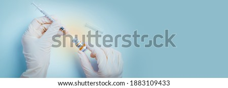 The power of science against COVID-19 Virus. Hand of doctor use a needle syringe to take a shot from vaccine vial. Global trial, Successful, Safe and effective vaccines. Banner, Close up, Blue