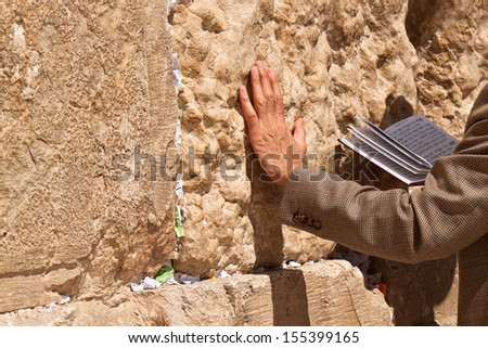The praying with a book in his hand leaning against the Wailing Wall