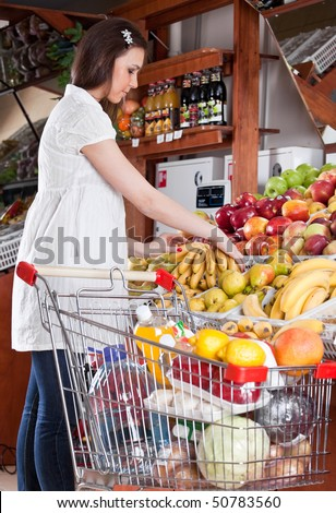 The pregnant girl chooses food in a supermarket