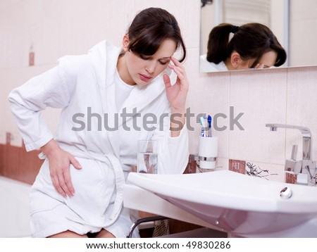 The pregnant woman with a strong toxicosis sitting in bathroom
